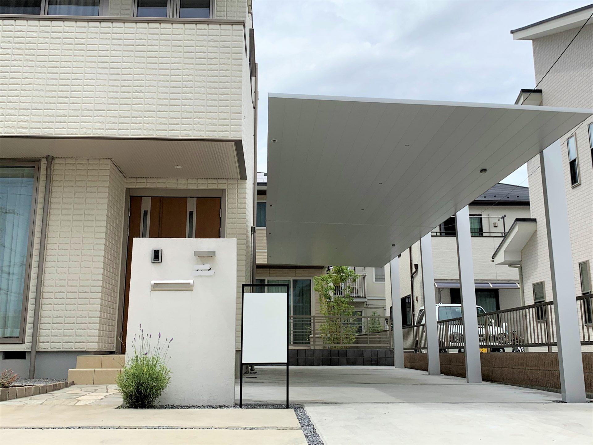 シンプルなデザインの宅配ポストとカーポートの写真