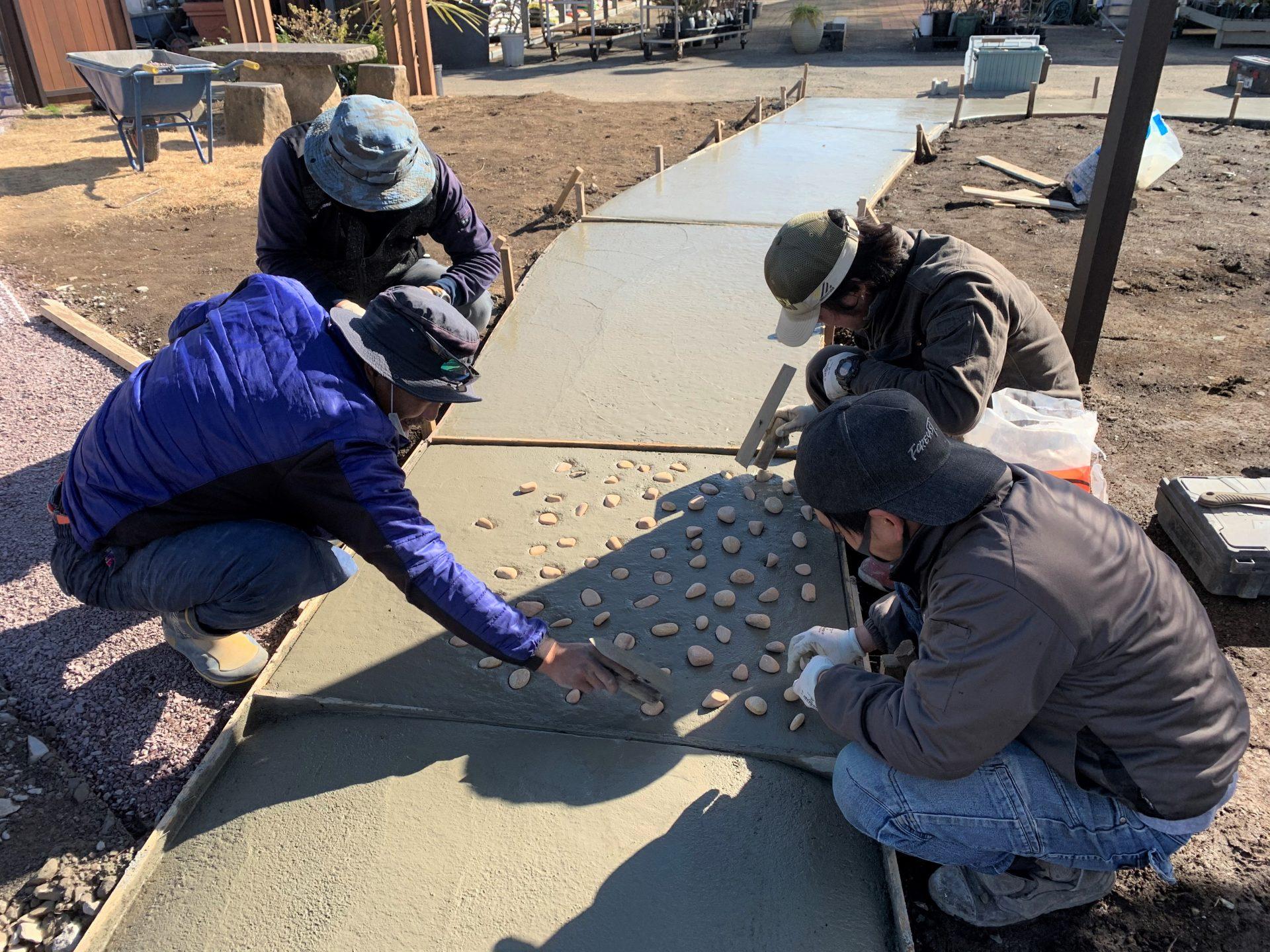 土間コンクリートに大きめの砂利をうめこむ作業