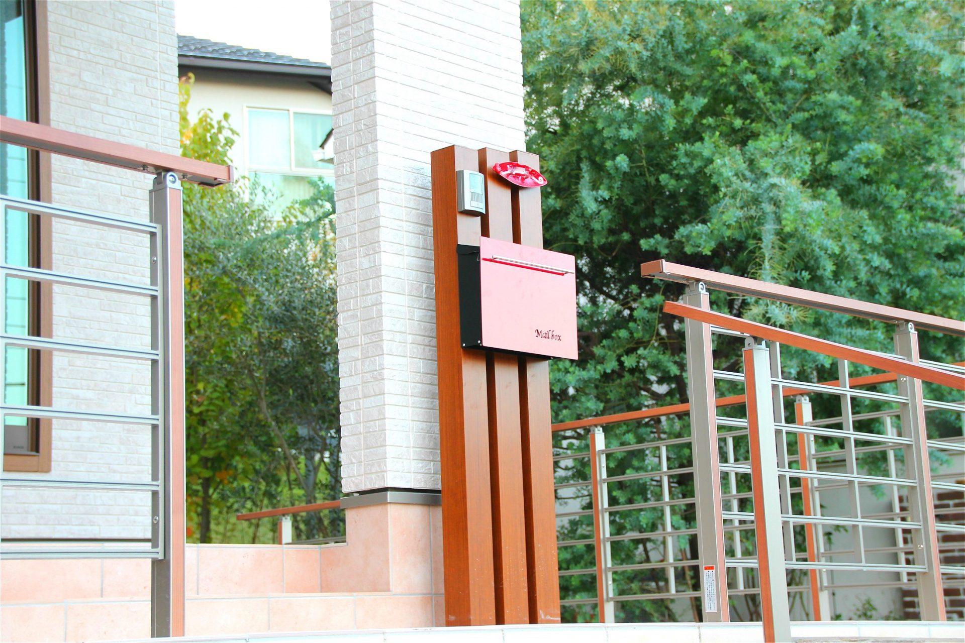 赤いポストがかわいい枕木材の門柱