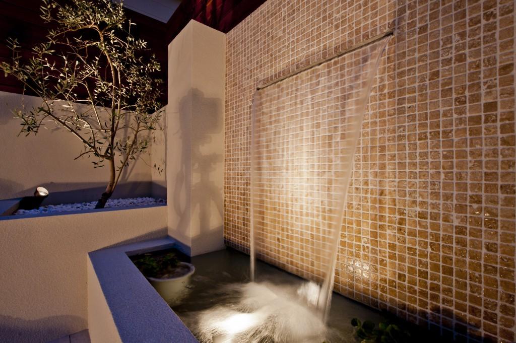 ライトアップされた壁泉とオリーブ