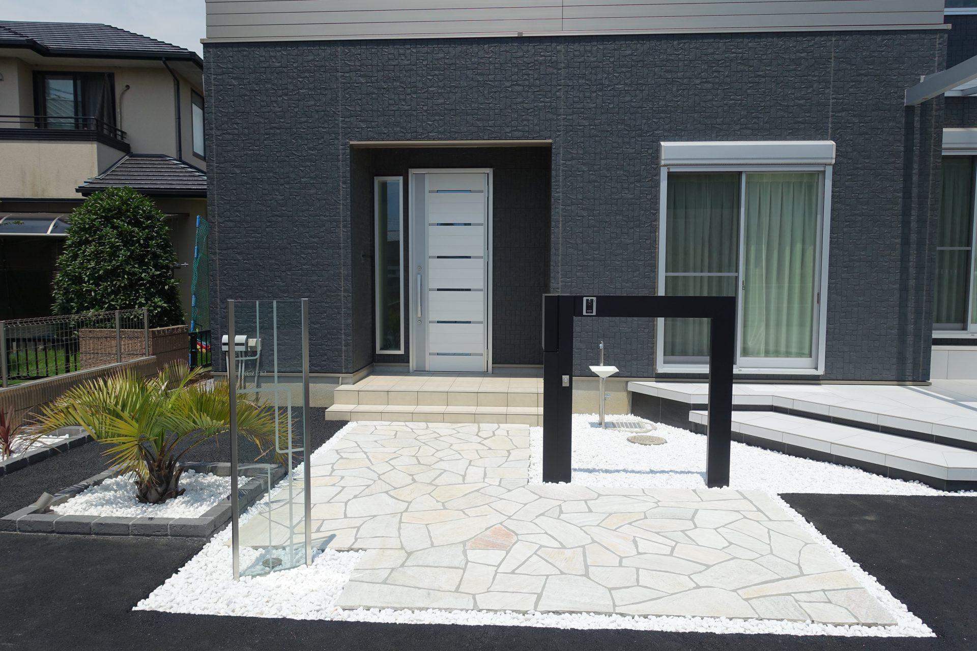 ガラスの独立表札と黒いフレームの様な門柱
