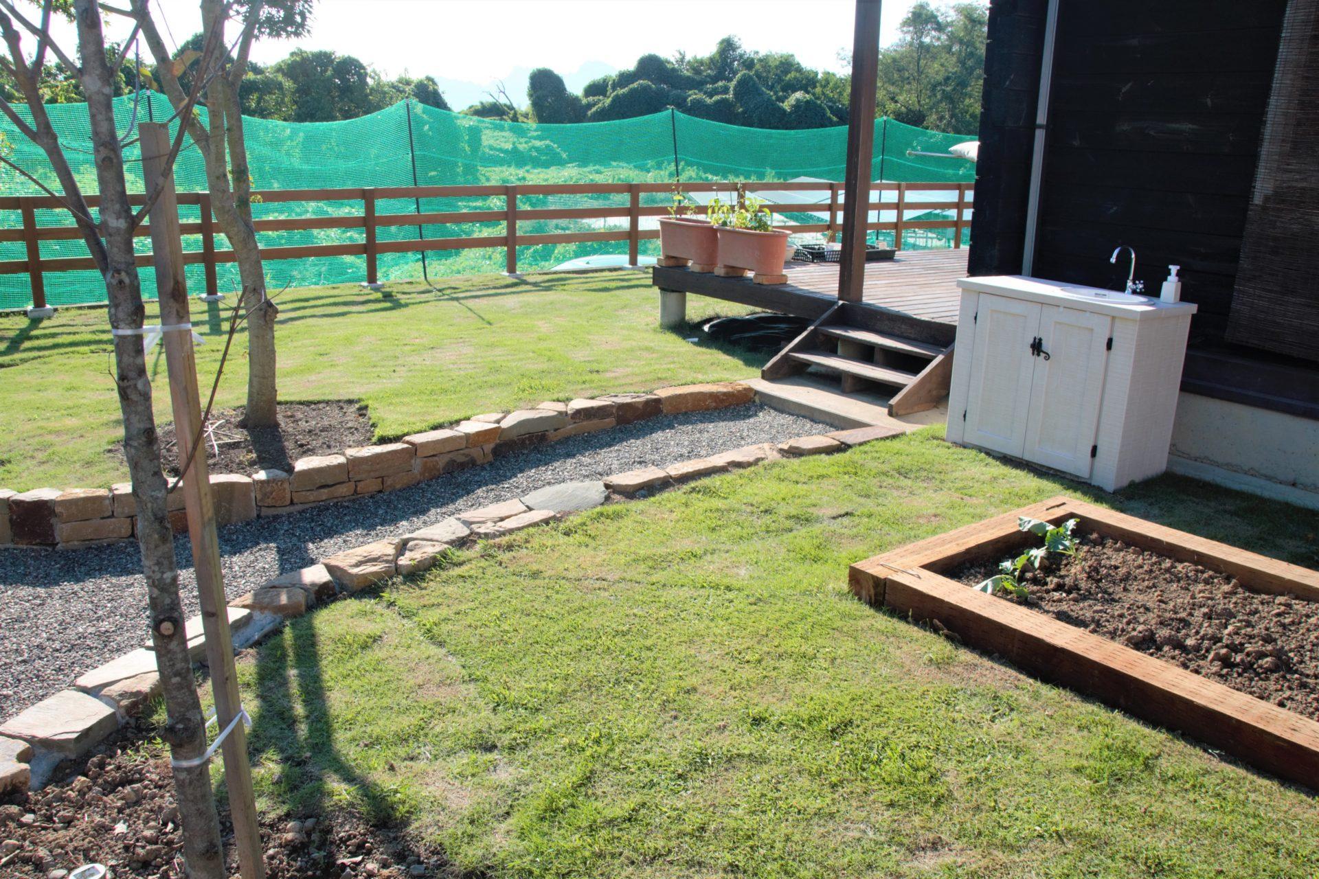 枕木で仕切られた菜園スペースとオシャレなガーデンシンク