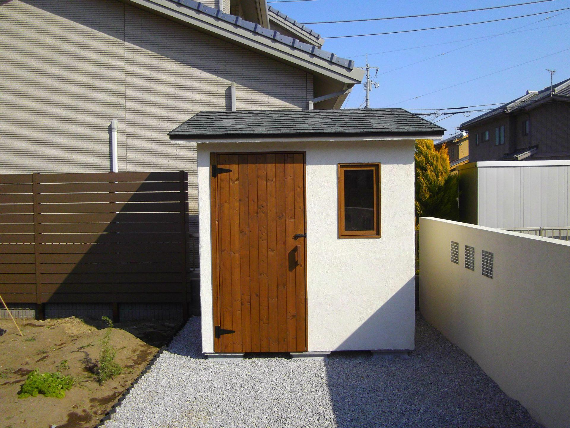 木製の扉と白いジョリパット仕上げの物置