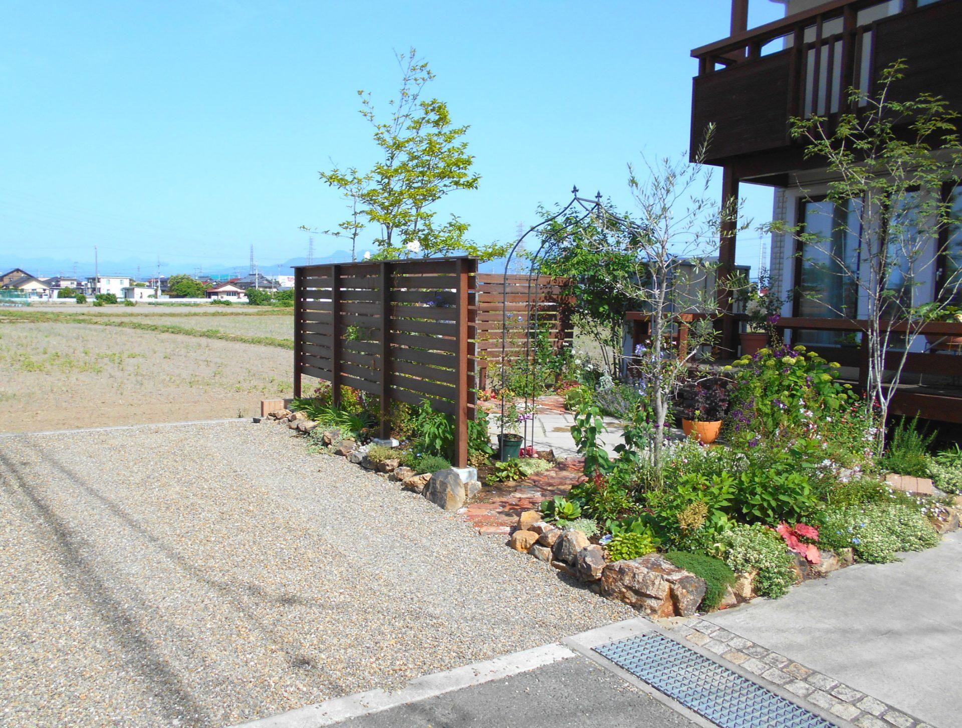 砂利敷きの駐車場と木製フェンスの風よけ