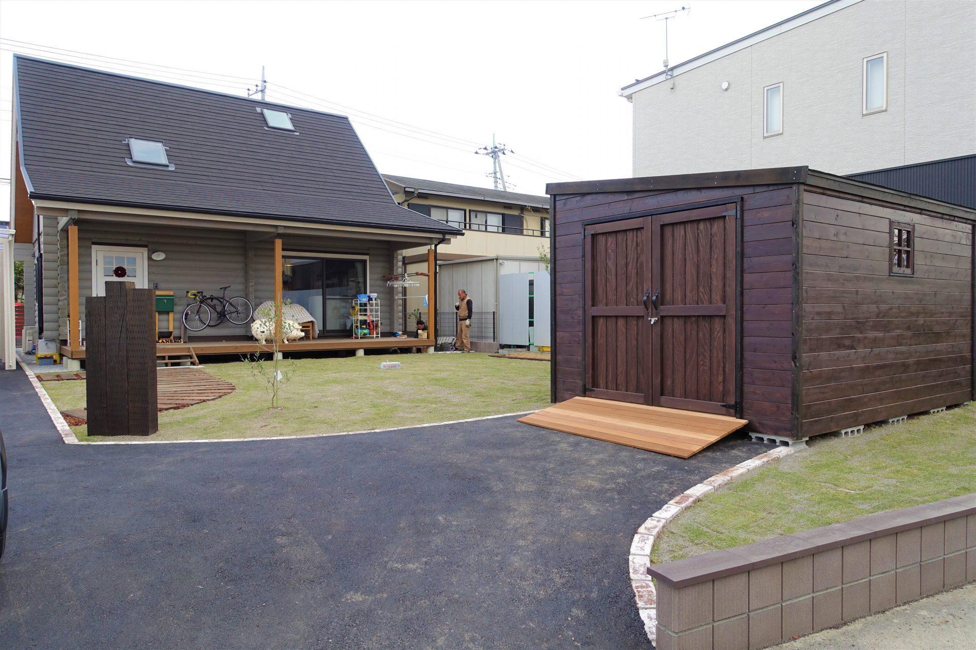 舗装駐車場と木製ガレージ