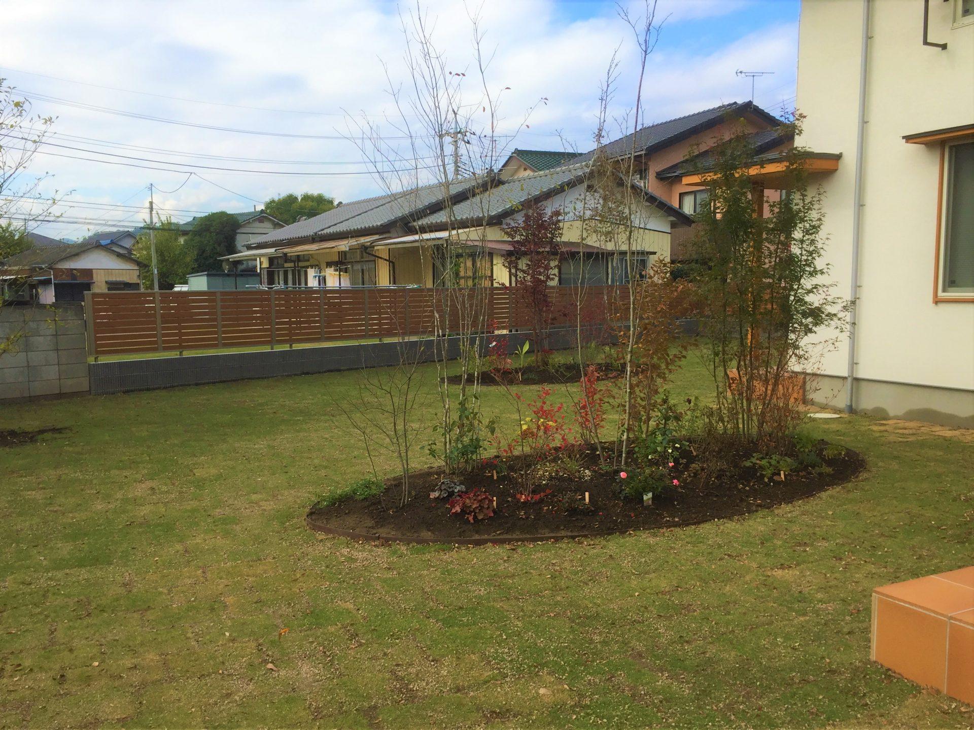 雑木風の植栽と広い芝の庭の写真