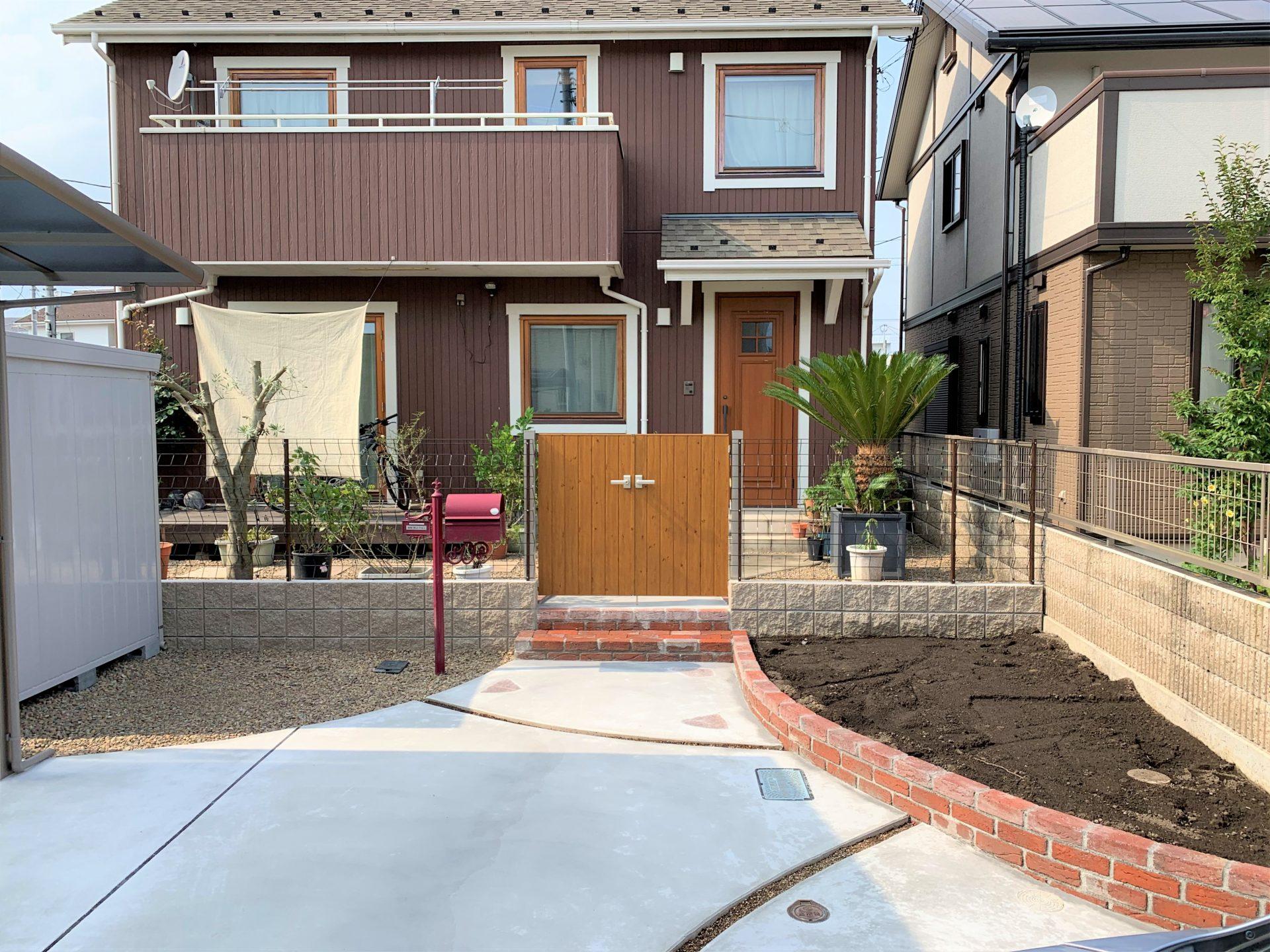 木目門扉と赤いポストとレンガ積み花壇
